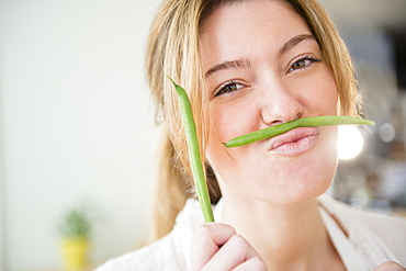 Portrait of blond woman holding green beans