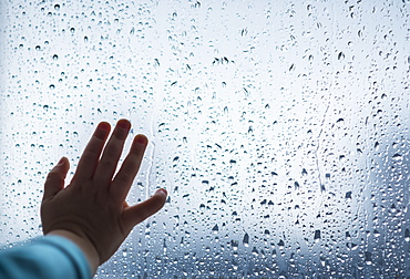 Close-up of girl's hand on wet window