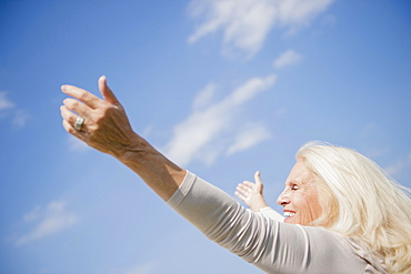 Senior woman with arms outstretched against sky