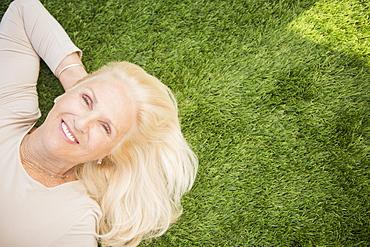 Senior woman lying on grass