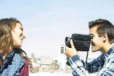 Man filming his girlfriend on roof, Brooklyn, New York