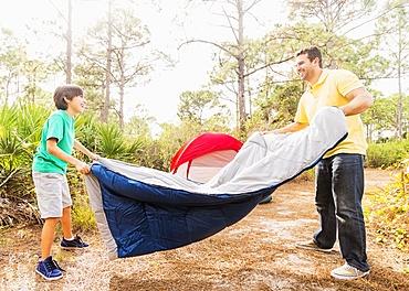 Father and son (12-13) preparing sleeping bag for camping, Jupiter, Florida