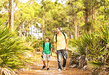 Father and son (12-13) walking through forest, Jupiter, Florida