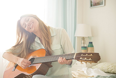 Young woman playing acustic guitar on bed