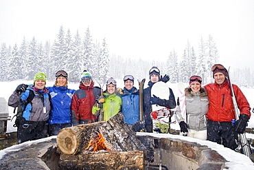 Portrait of group of friends with bonfire in winter, Whitefish, Montana, USA