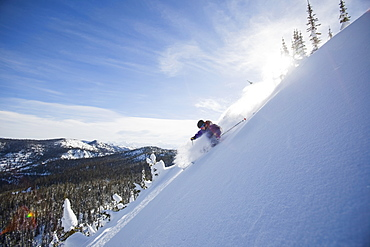 View of young man skiing in snowcapped mountains, Whitefish, Montana, USA