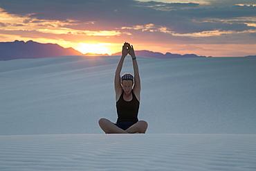 Mid-adult woman doing yoga in desert, White Sands National Monument, Alamogordo, New Mexico