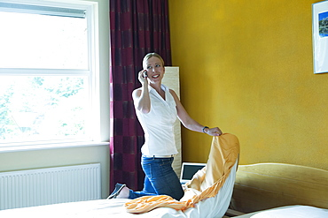 Netherlands, Goirle, Mid-adult woman making bed and talking on phone