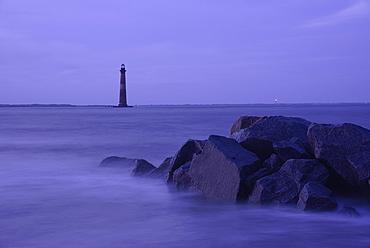 Coastal rocks and lighthouse silhouetted as dusk, Morris Island Light, Folly Beach, South Carolina