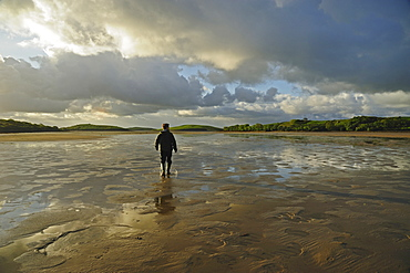 Rear view of man standing water in rubber boots, clouds in sky, Clew Bay, County Mayo, Ireland