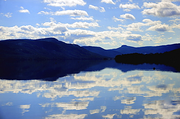 Symmetrical view of blue sky and clouds reflecting in lake, Lake George, New York