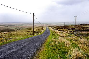 Rural country road runs through barren countryside, Rural County Mayo, Ireland