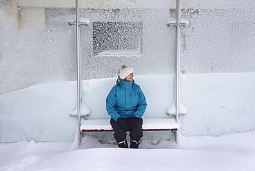 Middle aged woman sitting in bus stop, winter snow, Boston, Massachusetts
