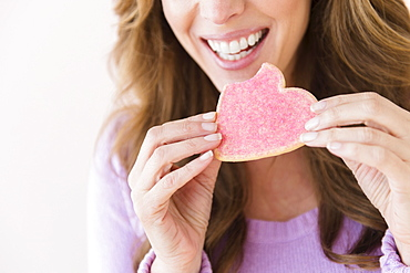 Woman holding heart shape cookie