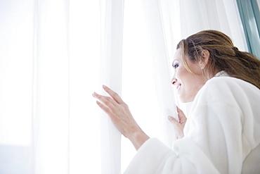 Woman wearing bathrobe looking through window