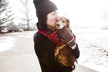 Woman holding and kissing dog, Colorado, USA