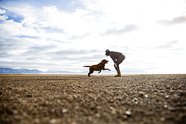 Woman playing with dog outdoors, Colorado, USA