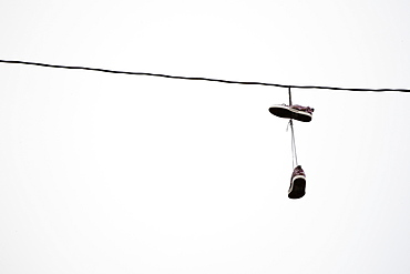 Shoes hanging in power line
