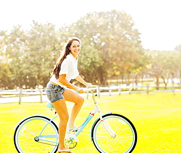 Young woman riding bicycle in park, Jupiter, Florida,USA