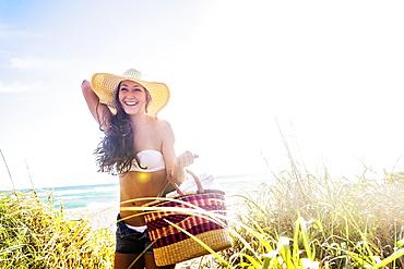 Woman in sunhat carrying basket on beach, Jupiter, Florida,USA