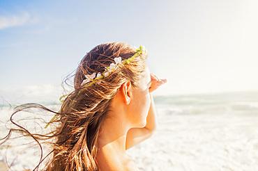 Woman on beach shielding eyes, Jupiter, Florida,USA