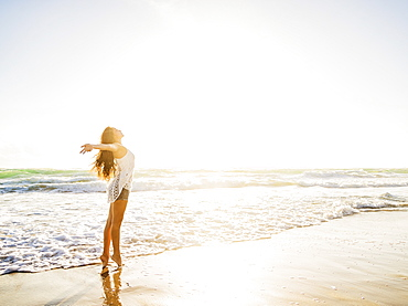 Woman on beach with arms raised, Jupiter, Florida,USA