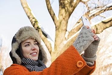 Woman taking selfie outdoors in winter, Brooklyn, New York,USA
