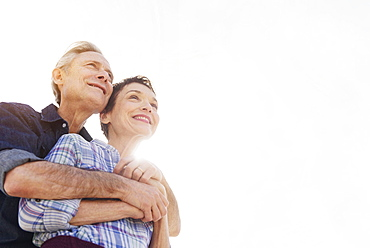 Smiling senior couple embracing in sunlight