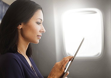 Young woman using tablet on plane
