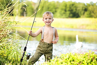Smiling boy (4-5) holding fishing rod, USA, New Jersey, Oldwick