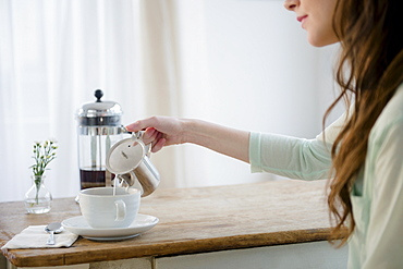 Young woman pouring milk into coffee cup