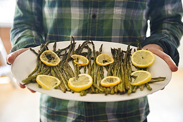 Man holding platter with asparagus and lemon