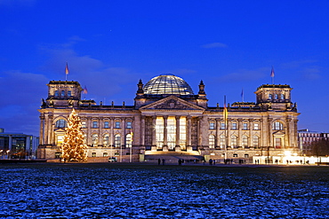 Illuminated Bundestag building and snowy lawn, Germany, Berlin, Reichstag building