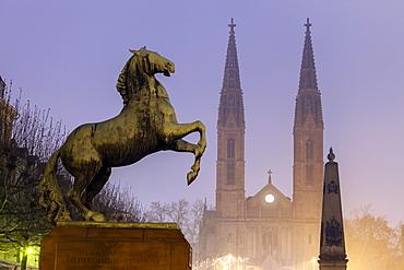 Horse sculpture of Waterloo Memorial and St. Boniface Church in mist, Germany, Hesse, Waterloo Memorial on Luisenplatz, St. Boniface Church