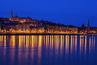 Illuminated skyline reflecting in Danube River, Hungary, Budapest, Matthias Church,Fisherman's Bastion, Danube River