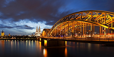 Hohenzollern Bridge illuminated at dusk, Germany, Cologne, Hohenzollern Bridge, Great St. Martin Church, Cologne Cathedral