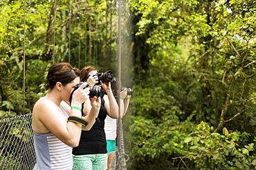 Young women photographing in forest, Costa Rica