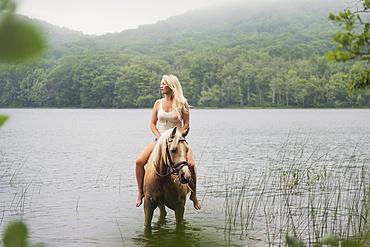 Woman horseback riding in countryside