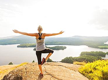 Rear view of young woman exercising outdoor, USA, Maine, Camden