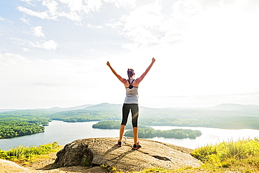 Young woman standing on top of mountain with outstretched arms, rear view, USA, Maine, Camden