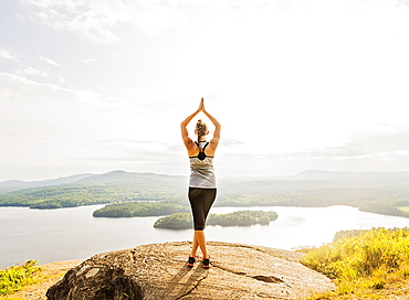 Rear view of young woman practicing yoga in front of lake, USA, Maine, Camden