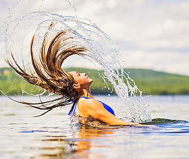 Young woman tossing hair back in lake