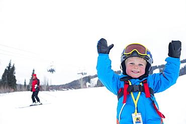 Smiley little boy (5) wearing ski suit in mountains, USA, Montana, Whitefish