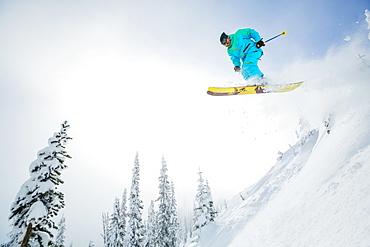 Young man jumping from ski slope, USA, Montana, Whitefish