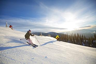 Three people on ski slope at sunlight, USA, Montana, Whitefish