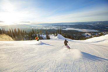 Two people on ski slope at sunlight, USA, Montana, Whitefish