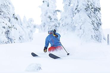 Mature man speeding on ski slope, USA, Montana, Whitefish