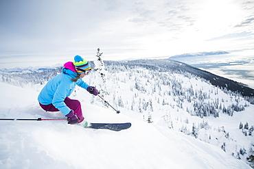Mature woman speeding on ski slope, USA, Montana, Whitefish