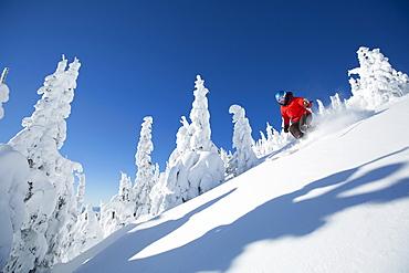 Low angle view of mature woman on ski slope , USA, Montana, Whitefish