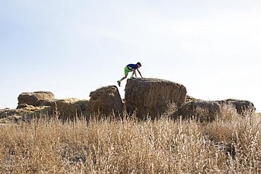 Boy (6-7) walking on bale of hay